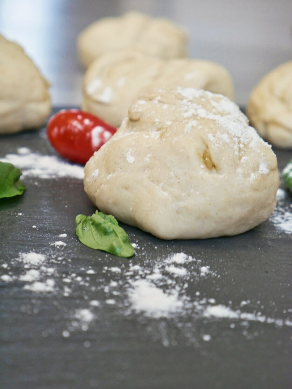 ball of uncooked pizza dough with flour on it