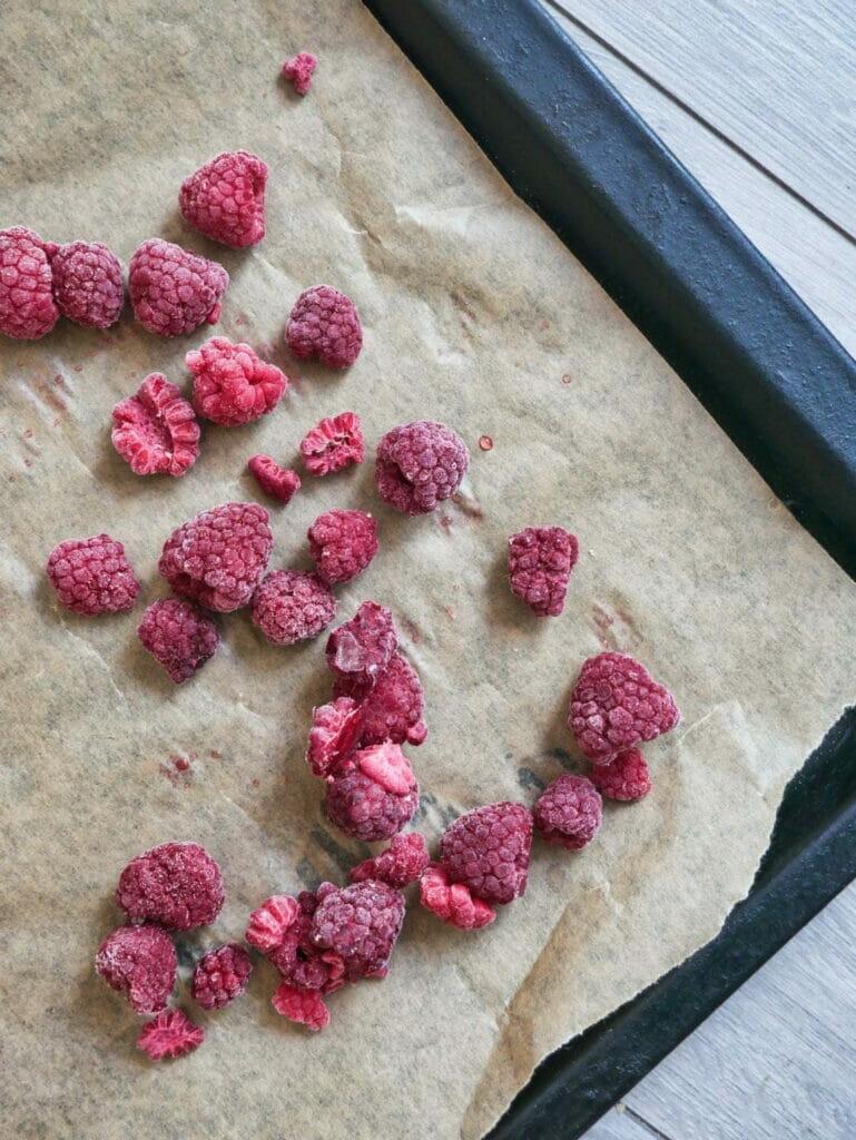 frozen raspberries on parchment paper
