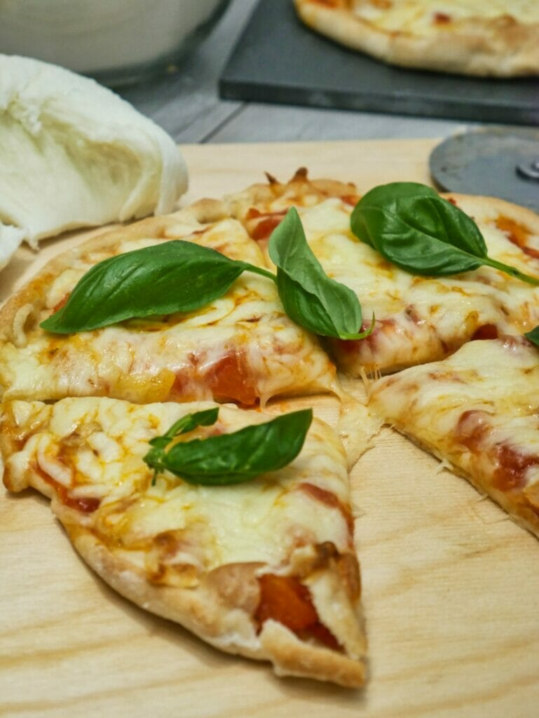 individual pizza with basil leaves