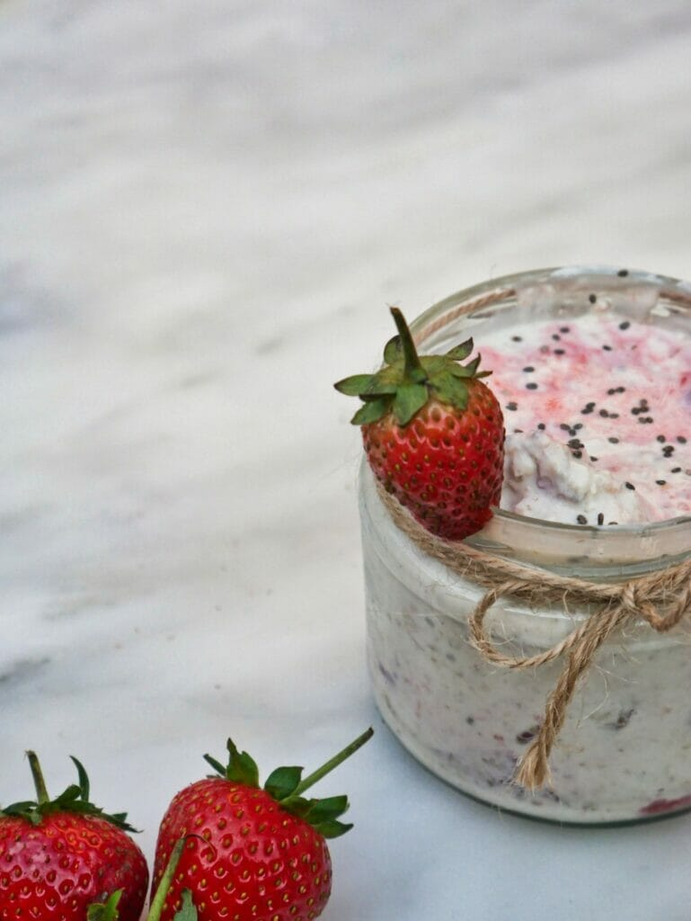 strawberry overnight oats with strawberry on rim