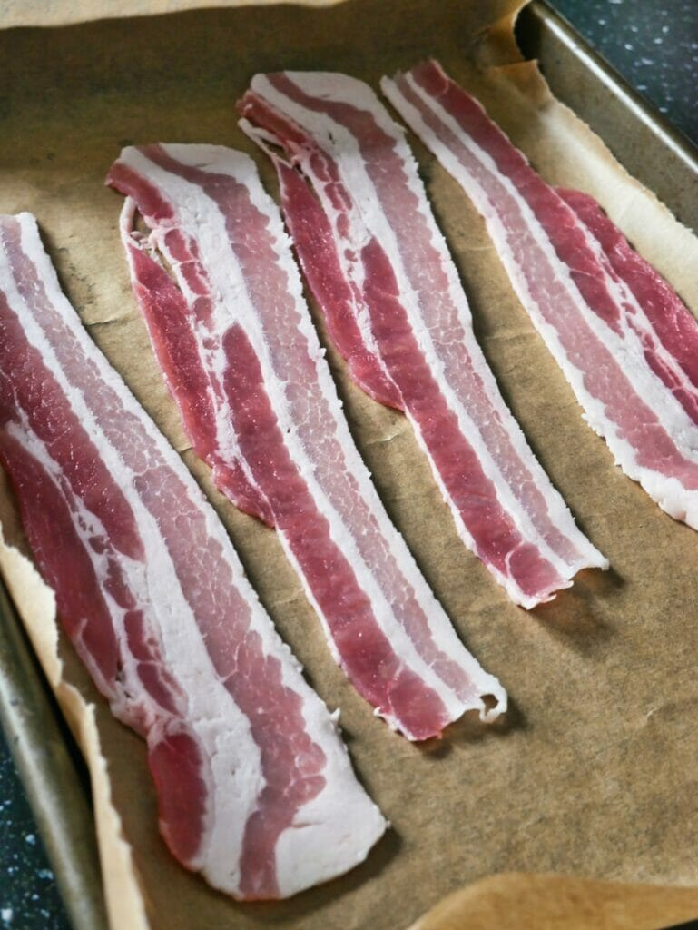 raw bacon on parchment paper